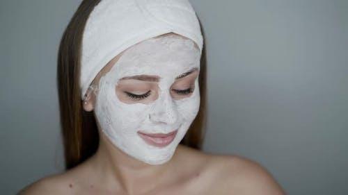 Frau mit kosmetischer Maske auf Gesicht sieht aus und posiert vor der Kamera auf neutralem Hintergrund