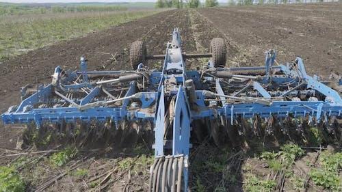 Disking the soil. Short disc harrow.