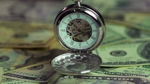 Watch and money closeup, the pendulum of fate. Importance of time over finances