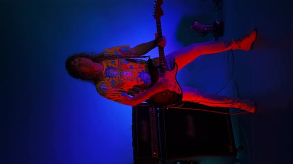Thumbnail for Vertical Video of a Crazy Jumping Rock Guitarist with a Guitar in His Hands on a Colored Neon