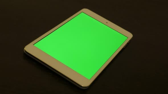 Thumbnail for Silver PC tablet with green screen display on wooden table 4K 2160p UltraHD footage - Silver tablet