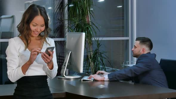 Thumbnail for Businessman Working on Laptop, Businesswoman Using Smartphone in Office