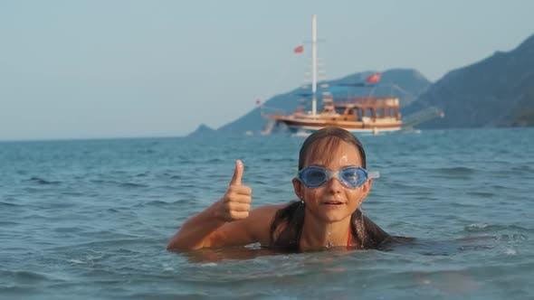 Thumbnail for Girl Emerging From Sea and Showing Thumb. Joyful Kid Bathing Into Sea