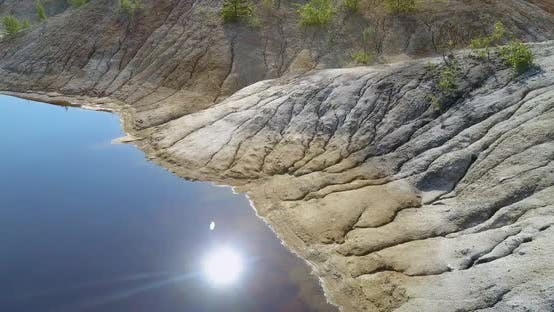 Thumbnail for Aerial Motion Along Mirror Lake with Reflected Sun and Cloud