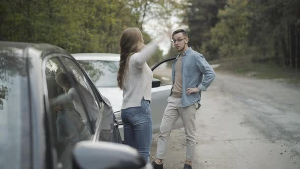 Young Stressed Man and Woman Yelling and Gesturing on Roadside