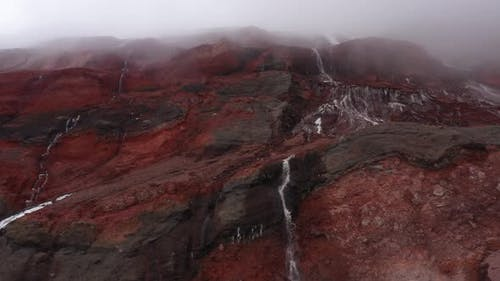 Close up showing a large waterfalls from meltwater with the gletser in the background