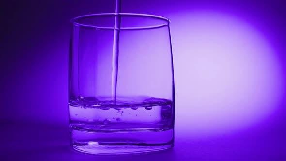 Thumbnail for Studio Shooting of Water Gießen in transparentes Glas auf blauem Hintergrund