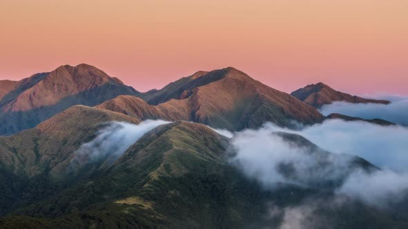 Thumbnail for Colors of sunset in mountains above misty clouds in New Zealand nature Time lapse