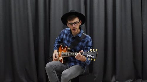Man performing solo and playing chords on guitar