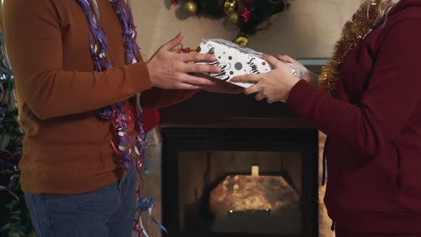 Close-up of Male Caucasian Hands Giving Christmas Gift To Woman. Young Wife or Girlfriend Taking