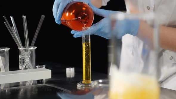 Cosmetics Manufacture Industry. Laboratory Assistants Mixing Ingredients in Glass Bottle Making Body