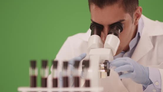 Thumbnail for Hispanic medical research scientist in lab using microscope on green screen