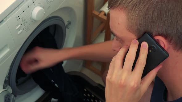 Young Man Takes Out Clothes From the Washing Machine and Calls with the Smartphone