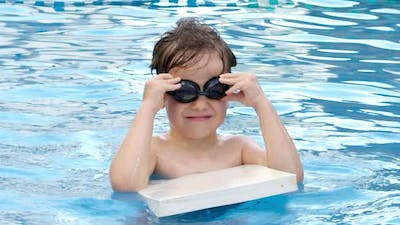 Cheerful Preschool Child Puts on Swimming Goggles for Swimming in the Pool