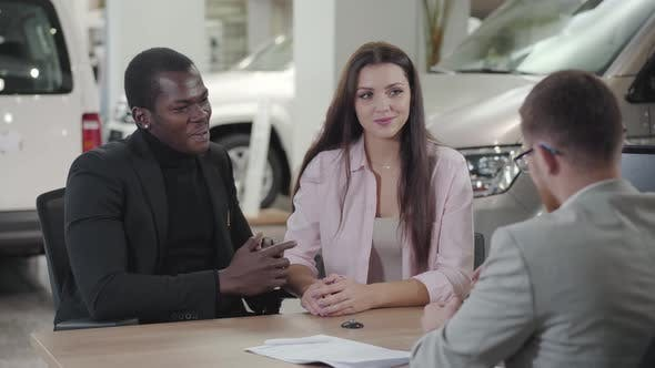 Thumbnail for Happy Young Multiracial Couple Sitting in Car Dealership and Talking with Salesman