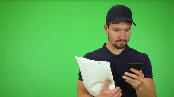 Thumbnail for A Young Handsome Mailman Works on a Smartphone, Then Smiles at the Camera - Green Screen Studio