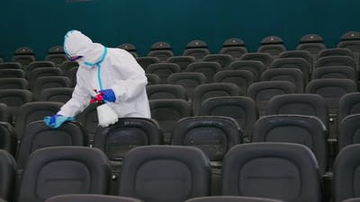 Man in Special Clothes Making Disinfection of Cinema