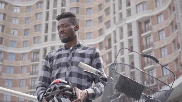 Thumbnail for Handsome African American Man Standing with Bicycle in Front of High Building Skyscraper Holding
