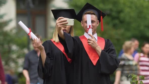 Thumbnail for Man and Woman in Academic Dresses Taking Selfie After Graduation Ceremony