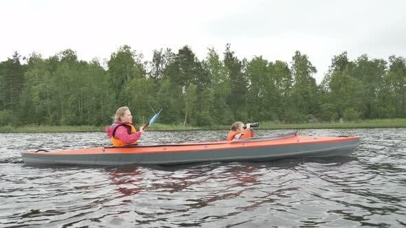 Thumbnail for Mother Rows Kayak While Daughter Looks Through Binoculars