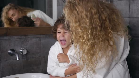 Thumbnail for Young Mum in White Coat Combing Her Curly Hair Her Cheerful Five Aged Son in Bathroom