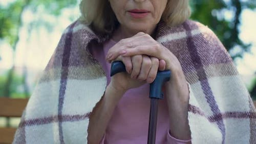 Lonely Old Lady Covered With Plaid Blanket Sighs Sadly Leaning on Walking Stick