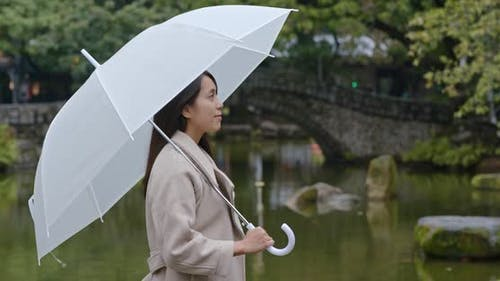Woman bring of umbrella in the park