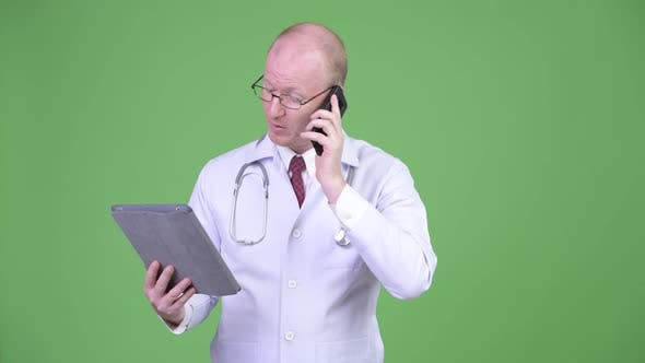 Thumbnail for Mature Bald Man Doctor Talking on the Phone While Using Digital Tablet