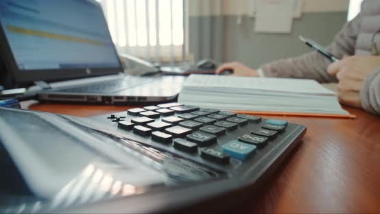 Close Up of Woman Hands Working on Laptop and Calculator, Counting Checks.