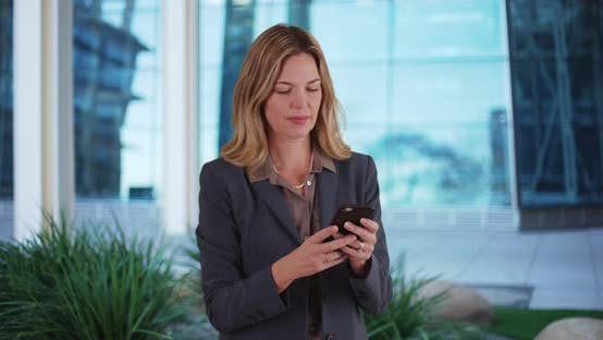 Thumbnail for Professional woman texting or messaging on smartphone outside office building