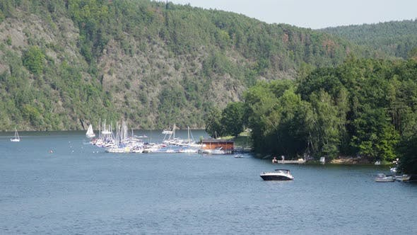 Cover Image for Boats Docked at a Dock on a Lake, Surrounded By Mountains, Forests and Nature.