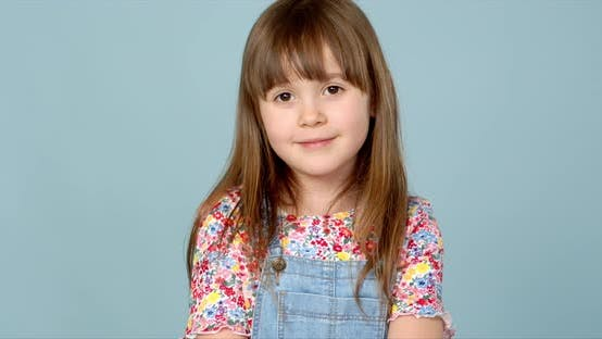 Thumbnail for Sweet Little Girl 6-7 Years Old Posing in Dungarees Jeans and Flower Pattern Blouse on Blue