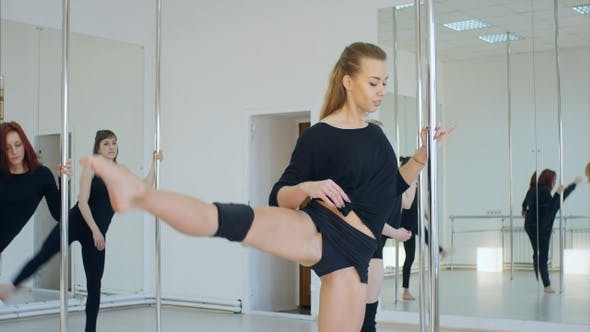 Thumbnail for Female Group Stretching Legsnear Pylon in A Studio