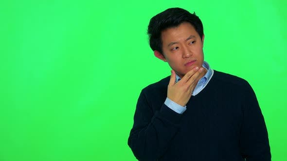 Thumbnail for A Young Asian Man Rubs His Chin Thinking About Something - Green Screen Studio