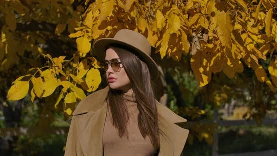 Thumbnail for Portrait of a Confident European Girl in Brown Hat and Sunglasses Standing on the Background of