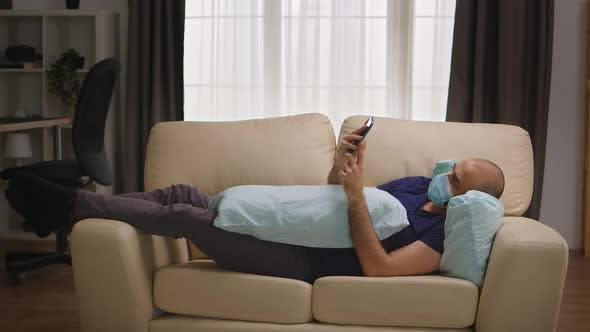 Thumbnail for Bored Man with Protection Mask Laying on Sofa
