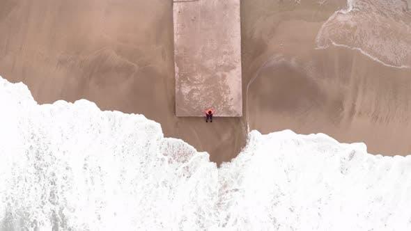 Sea waves crashing on sandy beach with concrete pier
