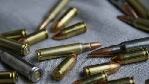 Cinematic rotating shot of bullets on a fabric surface - BULLETS 095