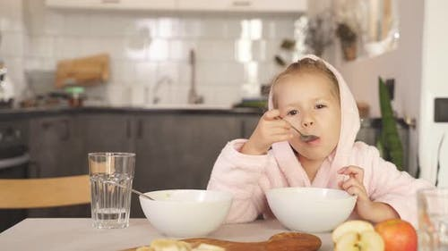 Girl with Blonde Hair Dressed in a Robe and Hood After a Shower Sits at the Table and Eats Oatmeal