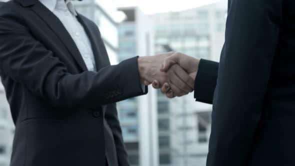Thumbnail for Cropped Shot of Businesswomen Shaking Hands on Street.