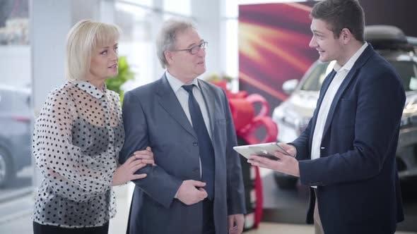 Senior Caucasian Couple Buying Automobile in Car Dealership
