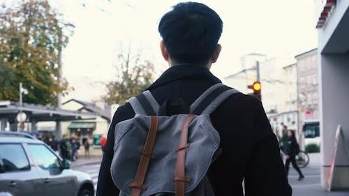 Young Asian Male Tourist Walking in City Centre in Europe