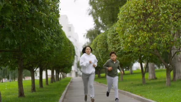 Thumbnail for Sportive Asian Mother and Son Jogging along Green Alley with Trees