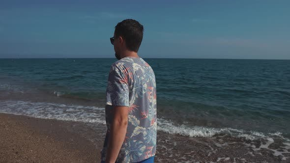 Relaxed Man Is Walking on Sea Pebble Beach in Sunny Summer Day, Back View