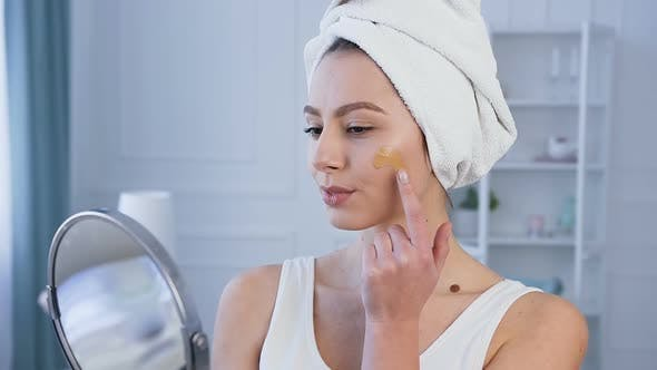 Cover Image for Beautiful Young Woman with Towel on Head Applying Concealer