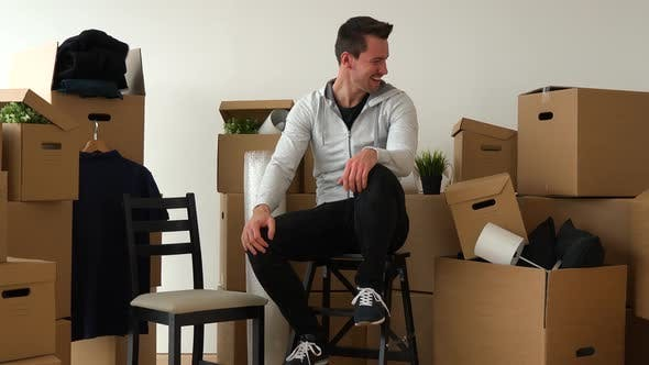 Thumbnail for A Happy Moving Man Sits on a Chair and Acts Ecstatic in an Empty Apartment, Surrounded By Boxes