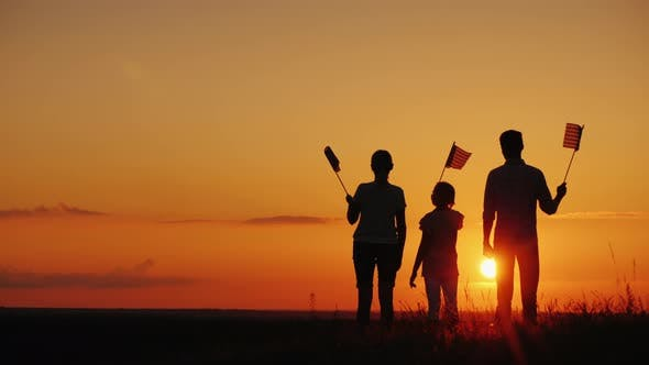 Thumbnail for A Group of People with Flags of America Looks at the Setting Sun
