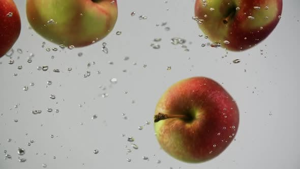 Thumbnail for Fresh Colorful Apples Green and Yellow Falling in Water Spinning with Air Bubbles White Background