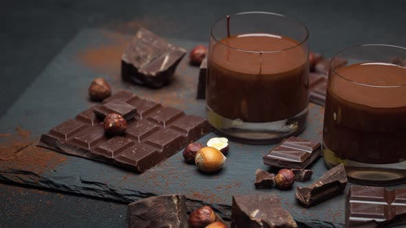 Thumbnail for Glass Bowl of Chocolate Cream or Melted Chocolate, Pieces of Chocolate and Hazelnuts