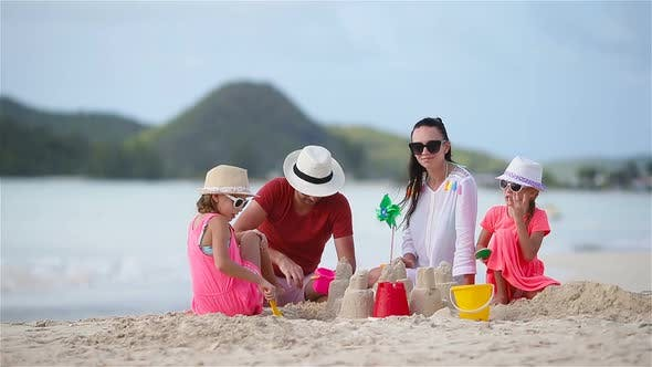 Thumbnail for Family of Four Making Sand Castle at Tropical White Beach